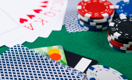 victorious layout of cards, on a green background, with poker chips and bank cards Stock Photo