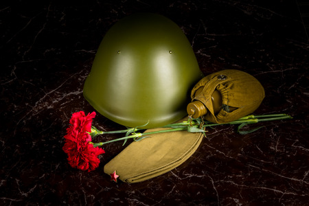 two carnations, a military helmet and a pilots cap, a flask, against the background of the monument