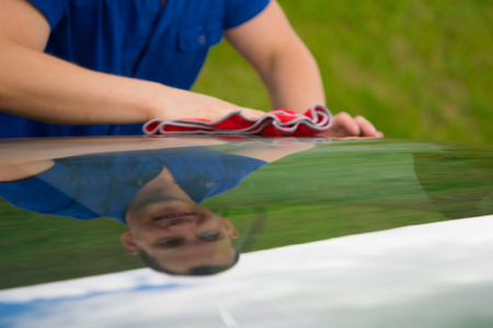 a car wash worker, wipes the car with a red rag with mappings