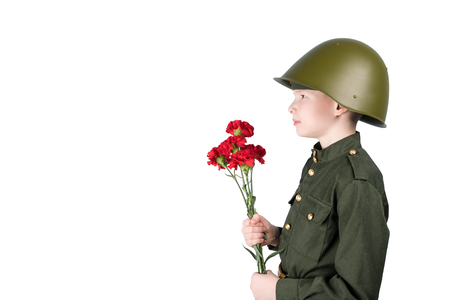 a boy in a helmet wearing a military uniform stands facing sideways and holding red flowers, isolated on white