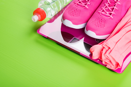 pink sport sneakers and a vest on the scales, and a bottle of water, on a light green background