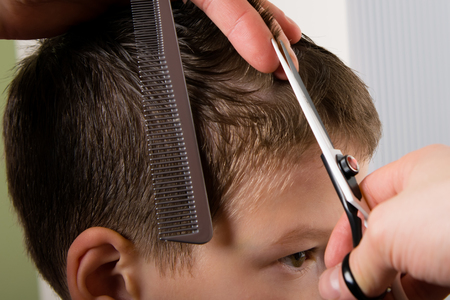 The hairdresser holds a comb and scissors in her hand and makes a hairdo boy