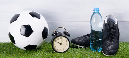 soccer ball, boots, water bottle, alarm clock, stand on the grass, on a gray background Stock Photo