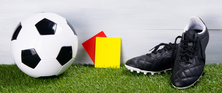 soccer ball, boots, penalty cards for the referee, lie on the grass, on a gray background