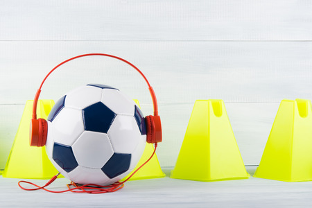 fence yellow cones on a gray background, behind a soccer ball, which is wearing red headphones
