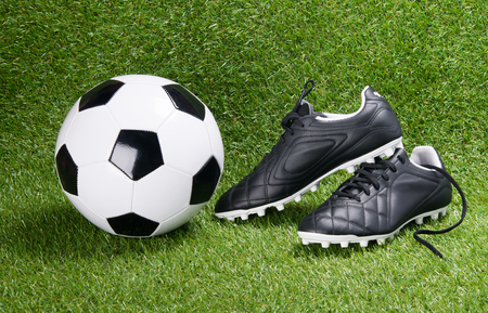 soccer ball and black boots, against the background of grass