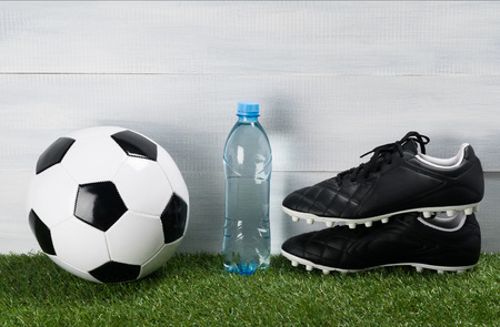 a bottle of water on a green lawn next to the ball and shoes for football