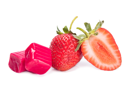 chewing candy next to a strawberry berry on a white background