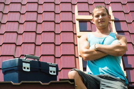 the man sits on the roof of the house next to the tool box