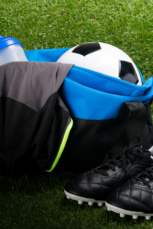 soccer ball in a sports bag and a T-shirt, black boots, on a grass background
