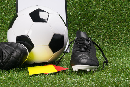 ball and shoes for football with a yellow and red card of the referee, on a green lawn