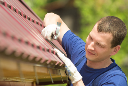 a man in a blue suit repairing the roof of the house, close-up Banco de Imagens
