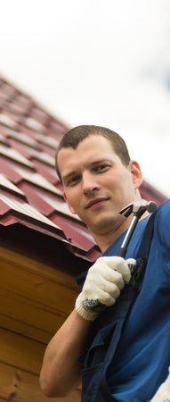 man repairing the roof holds a hammer in his hand on the background of the roof of the house