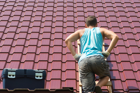 the man climbed onto the roof of the house with tools to repair it Banco de Imagens
