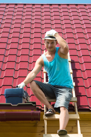 master comes down from the roof of the house with tools after repairing it