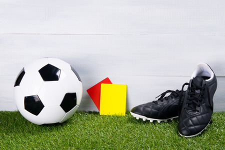 soccer ball, black boots and two penalty cards for the judge, stand on the grass, on a gray background Stock Photo