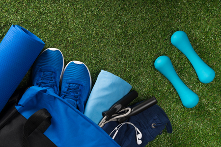 set of blue things for sports man training lies on green grass background