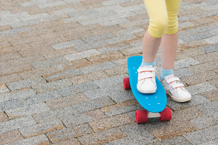 feet of a girl stand on a skateboard in a city park