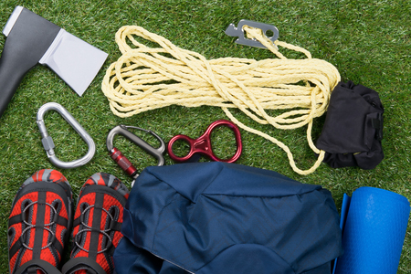 on the background of grass, a set of objects for outdoor activities, an ax, a rope and a backpack