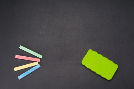on a black board is a multi-colored chalk for drawing and a sponge for erasing Banco de Imagens