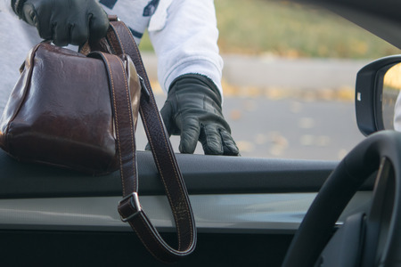 The thief steals a bag with documents through a window of the car, left by the owner