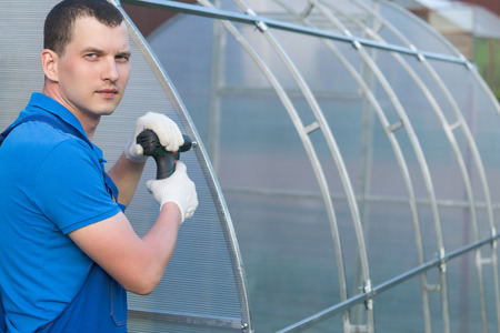 The master with the tool collects a greenhouse in the street Stock Photo
