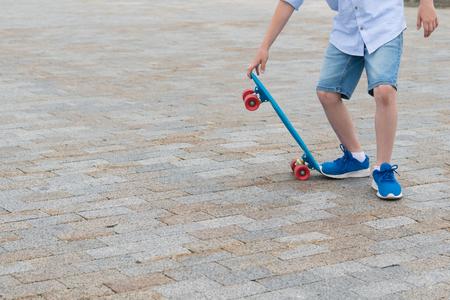 beautiful boy in asvalte does a skateboard trick
