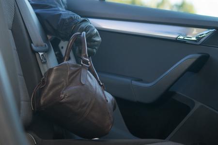 le voleur prend le sac avec les documents sur la banquette arrière de la voiture
