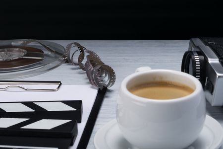 cup of coffee on the table with movie cameraman's things