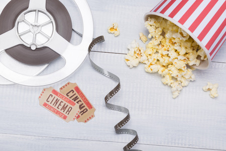paper cup with popcorn, scattered next to the film and tickets for a movie session Stock Photo