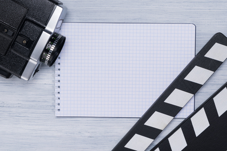 Clapperboard, camcorder and notebook for records are on the light background of the director's table Stock Photo