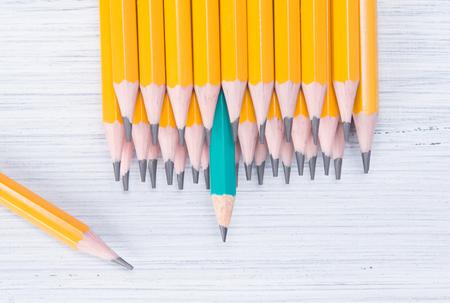 eine Reihe gelber einfacher Bleistifte auf hellem Hintergrund und ein grüner