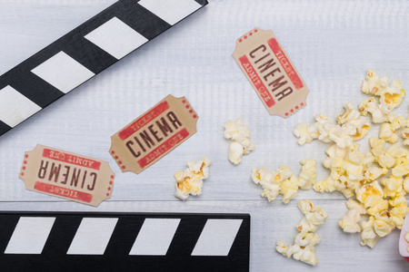 concept of movie tickets with grains of popcorn on a light background