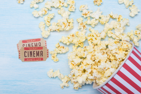 a pack of popcorn at the cinema and two movie tickets on a blue background Stockfoto