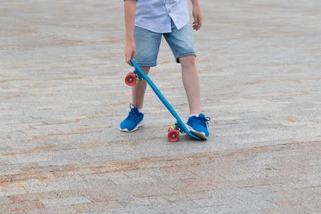 boy's legs are learning to handle a skateboard, close-up against the background of the road