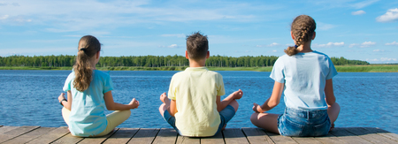 fitness exercises, yoga, three Teens sitting on the pier near the water outdoors Reklamní fotografie