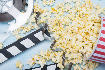 scattered paper cup popcorn with film, concept on blue background