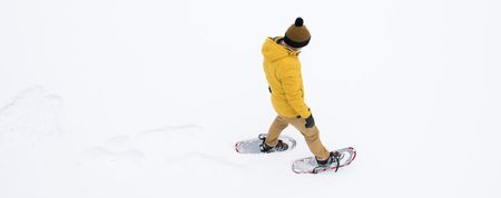 a man in winter, yellow clothes walking on white snow in snowshoes in the distance, there is a place for the inscription 版權商用圖片