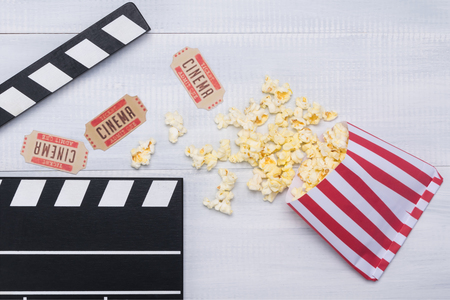 popcorn paper bag and movie tickets on a wooden table with a clapperboard for filming Stock Photo