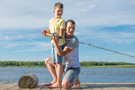 against the background of nature, the father teaches his son to throw a fishing rod for big fish
