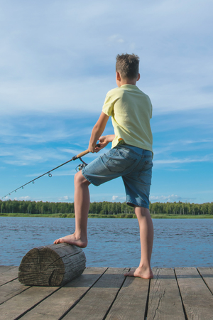 boy fishing on the pier, against the blue sky and the lake, rear view