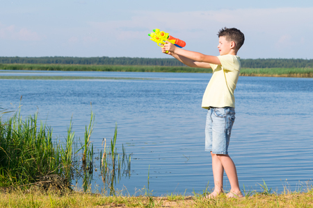 boy on the river playing with a water gun Stock Photo