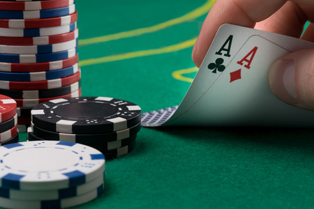 hand raises for two winning cards on a green poker table