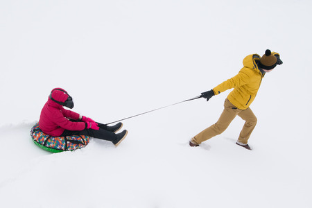 a man in a yellow jacket, looking into the distance and pulls the tubing with a girl in virtual reality glasses, white snow