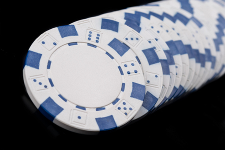 blue poker chips lie in a row on a black background