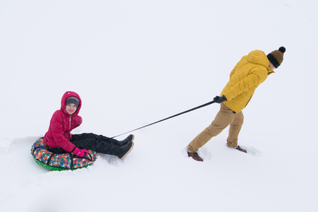 in the open air, on fresh snow, a man rolls his daughter on a tubing