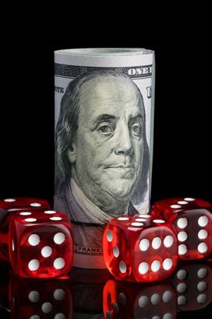 red transparent dice for gambling and a stack of money on a black background Foto de archivo