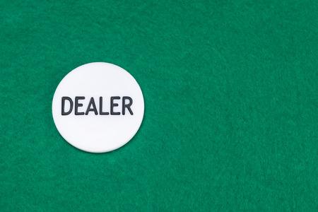 white chip dealer on a green poker table background