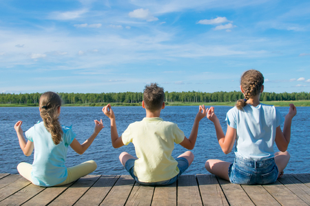 in the open air, on the pier, near the water, children are engaged in relaxation in the form of yoga Imagens