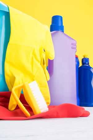 concept of detergents and rubber gloves for cleaning on yellow background close up